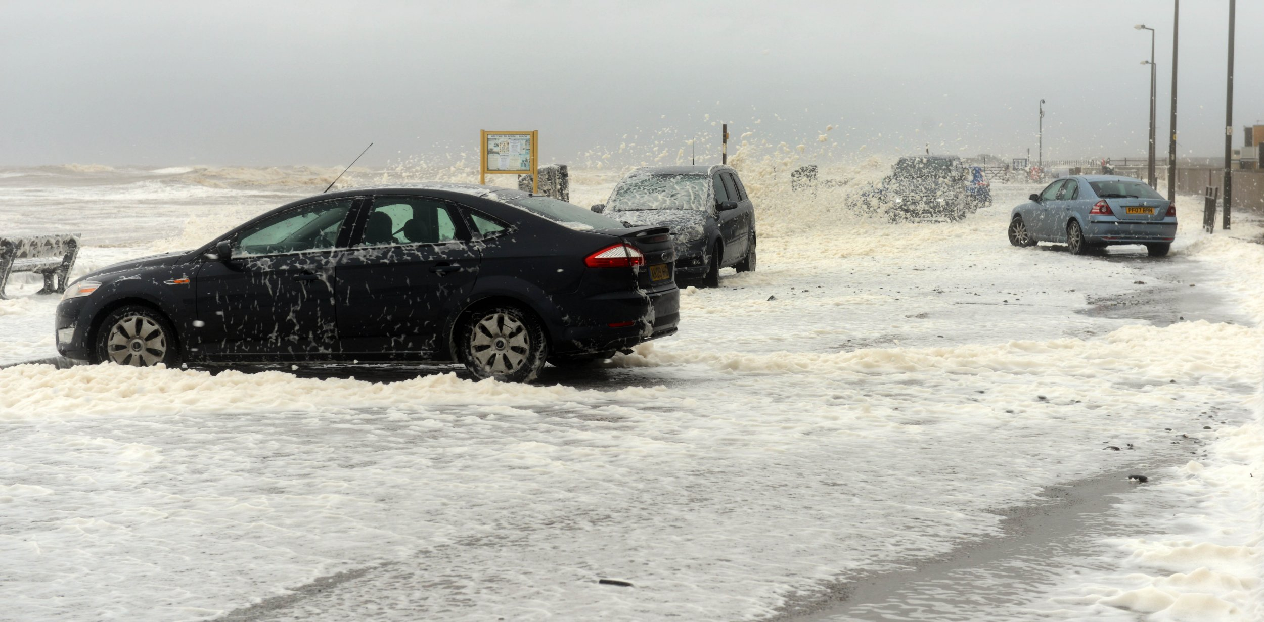 Foam from the sea covers cars in Cleveleys, Lancs., making driving conditions difficult. Heavy rain and gale-force winds are set to batter the UK with the arrival of the storm that brought severe blizzards to the US. The Met Office has issued a warning for heavy rain on Tuesday for the west of the UK, with 100mm (four inches) expected in parts of Wales and England. 26 January 2016.