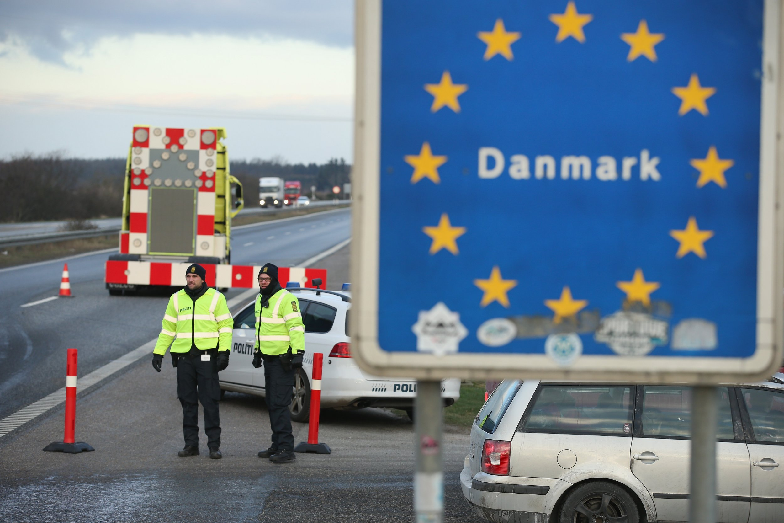 PADBORG, DENMARK - JANUARY 06: Danish police conducting spot checks on incoming traffic from Germany stand at the A7 highway border crossing on January 6, 2016 near Padborg, Denmark. Denmark introduced a 10-day period of passport controls and spot checks yesterday on its border to Germany in an effort to stem the arrival of refugees and migrants seeking to pass through Denmark on their way to Sweden. Denmark reacted to border controls introduced by Sweden the same day and is seeking to avoid a backlog of migrants accumulating in Denmark. Refugees still have the right to apply for asylum in Denmark and those caught without a valid passport or visa who do not apply for asylum are sent back to Germany. (Photo by Sean Gallup/Getty Images)