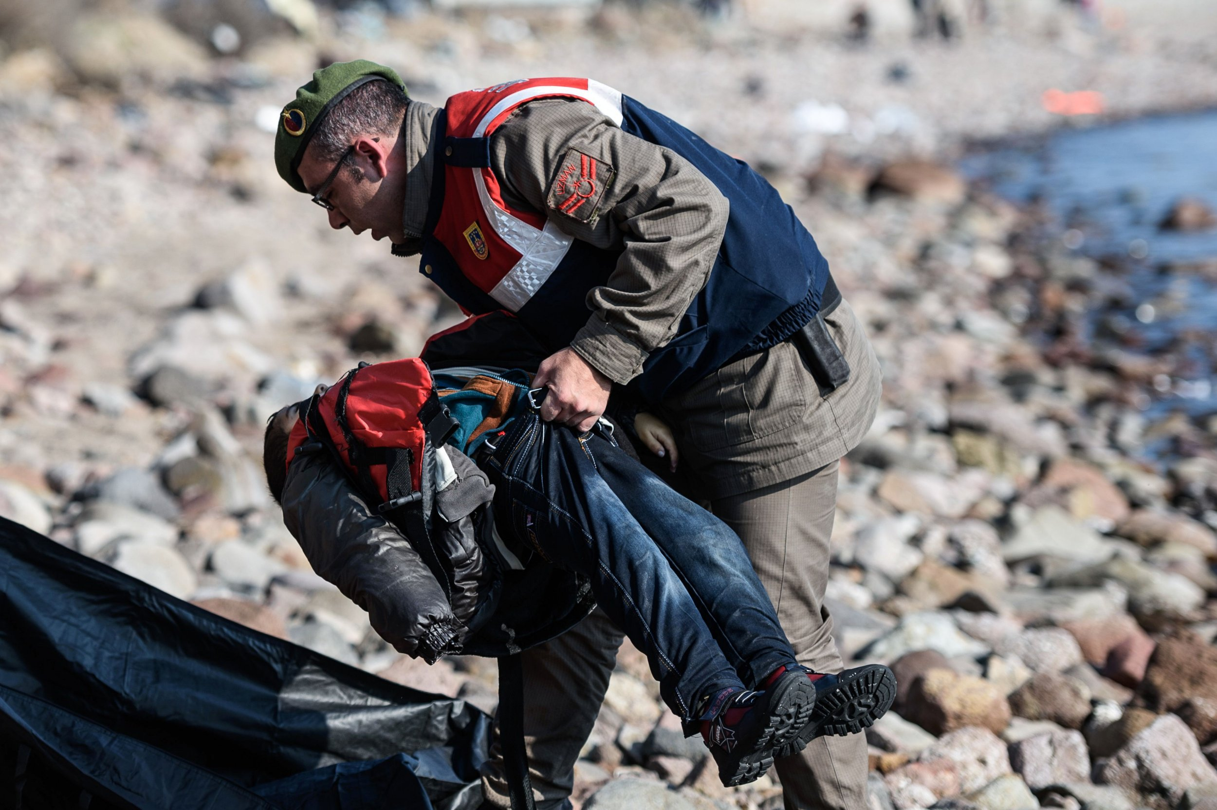 EDITORS NOTE: Graphic content / A Turkish gendarme carries the body of a child on a beach in Canakkale's Bademli district on January 30, 2016 after at least 33 migrants drowned when their boat sank in the Aegean Sea while trying to cross from Turkey to Greece, Turkey's state-run Anatolia news agency reported. The migrants, who included those from Myanmar, Afghanistan and Syria, set sail from the Canakkale province to reach the nearby Greek island of Lesbos, Anatolia said. / AFP / OZAN KOSEOZAN KOSE/AFP/Getty Images