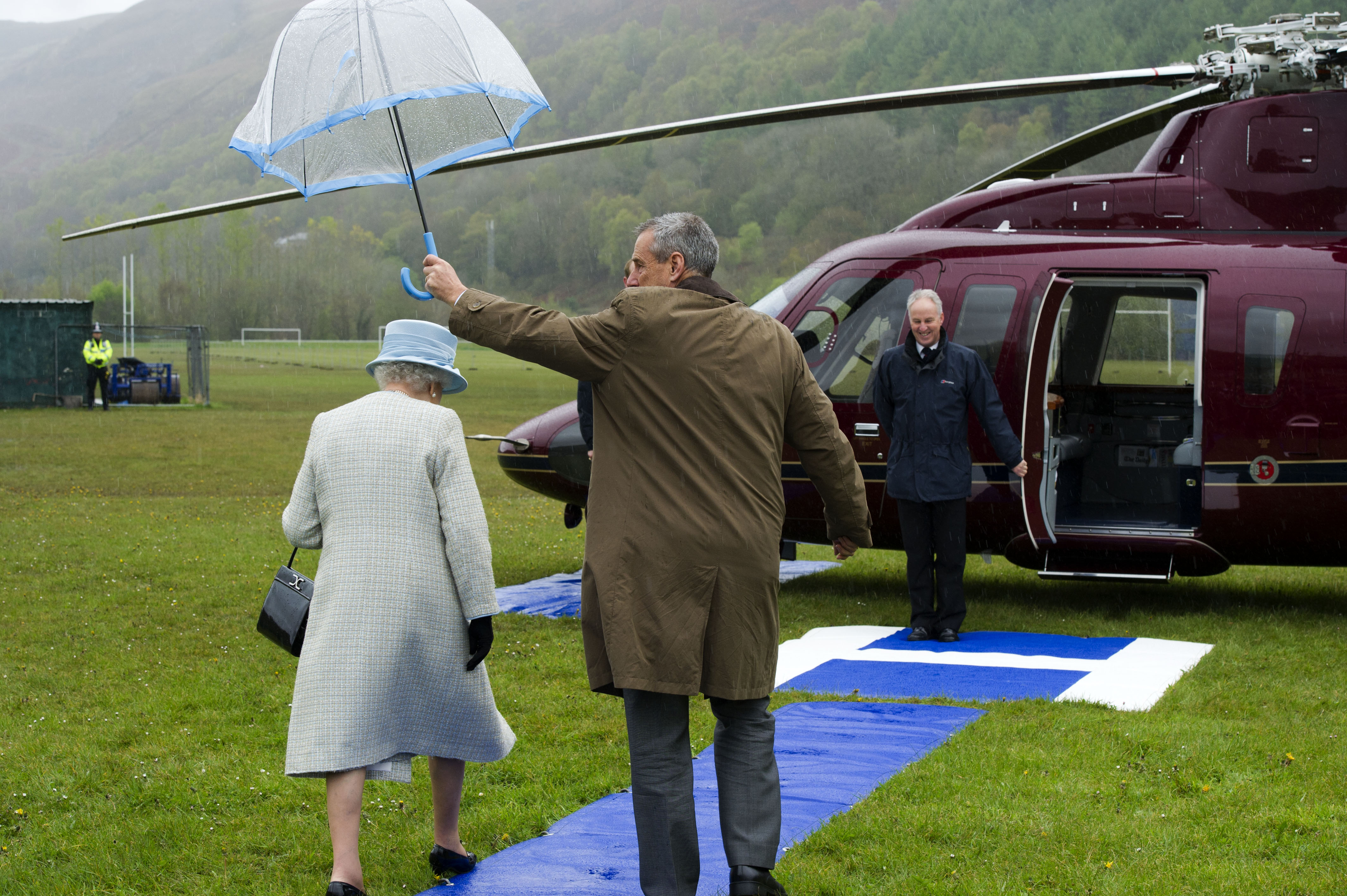 ABERFAN, WALES - APRIL 27: Queen Elizabeth II is sheltered by an umbrella as she walks to the royal helicopter after officially opening Ynysowen Community Primary School on April 27, 2012 in Aberfan, near Merthyr Tydfil in South Wales. As part of their Diamond Jubilee tour of the country, during their two day visit to Wales the Queen and Duke of Edinburgh made their fourth visit to the village of Aberfan since the community lost the lives of 116 children and 28 adults to the collapse of a colliery spoil tip in 1966. (Photo by Arthur Edwards - WPA Pool/Getty Images)