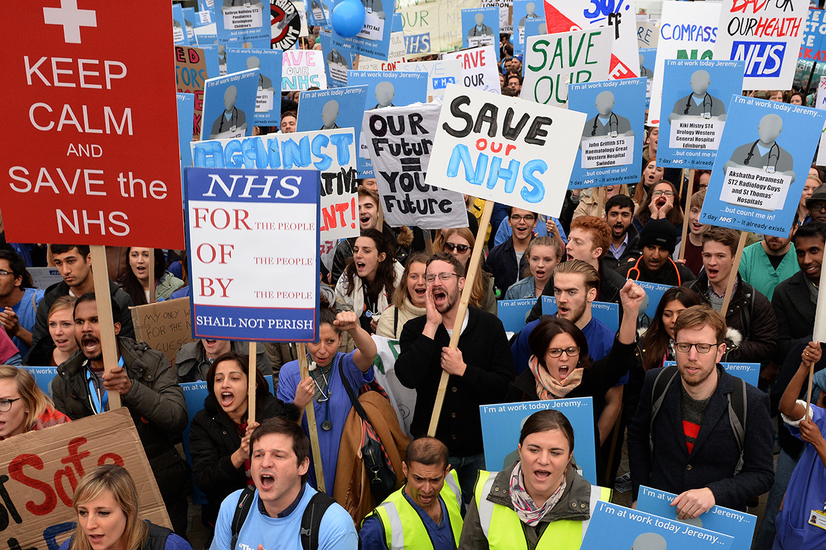 File photo dated 17/10/2015 of demonstrators listen to speeches in Waterloo Place during the 'Let's Save the NHS' rally and protest march by junior doctors in London. PA