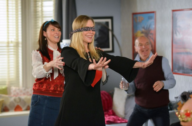 WARNING: Embargoed for publication until 00:00:01 on 23/02/2016 - Programme Name: Eastenders - TX: 01/03/2016 - Episode: 5238 (No. n/a) - Picture Shows: Honey encourages Ronnie to join in a party game. Honey (EMMA BARTON), Ronnie Mitchell (SAMANTHA WOMACK), Les Coker (ROGER SLOMAN) - (C) BBC - Photographer: Kieron McCarron