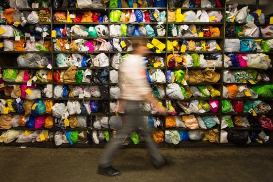 A member of staff walks past bags of clothing among the items at the Transport for London Lost Property Office, in central London, which sorts and stores the items left on London's public transport system. PRESS ASSOCIATION Photo. Issue date: Monday February 1, 2016. Last year 22% of the 302,714 items handed in were returned to their rightful owners including a brown envelope containing £15,000 and an urn of ashes that had been kept by workers at the lost property office for almost seven years. See PA story TRANSPORT Property. Photo credit should read: Dominic Lipinski/PA Wire