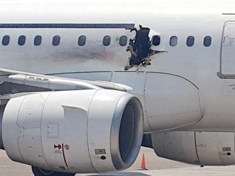 Man 'sucked out of hole in plane was suicide bomber in wheelchair'