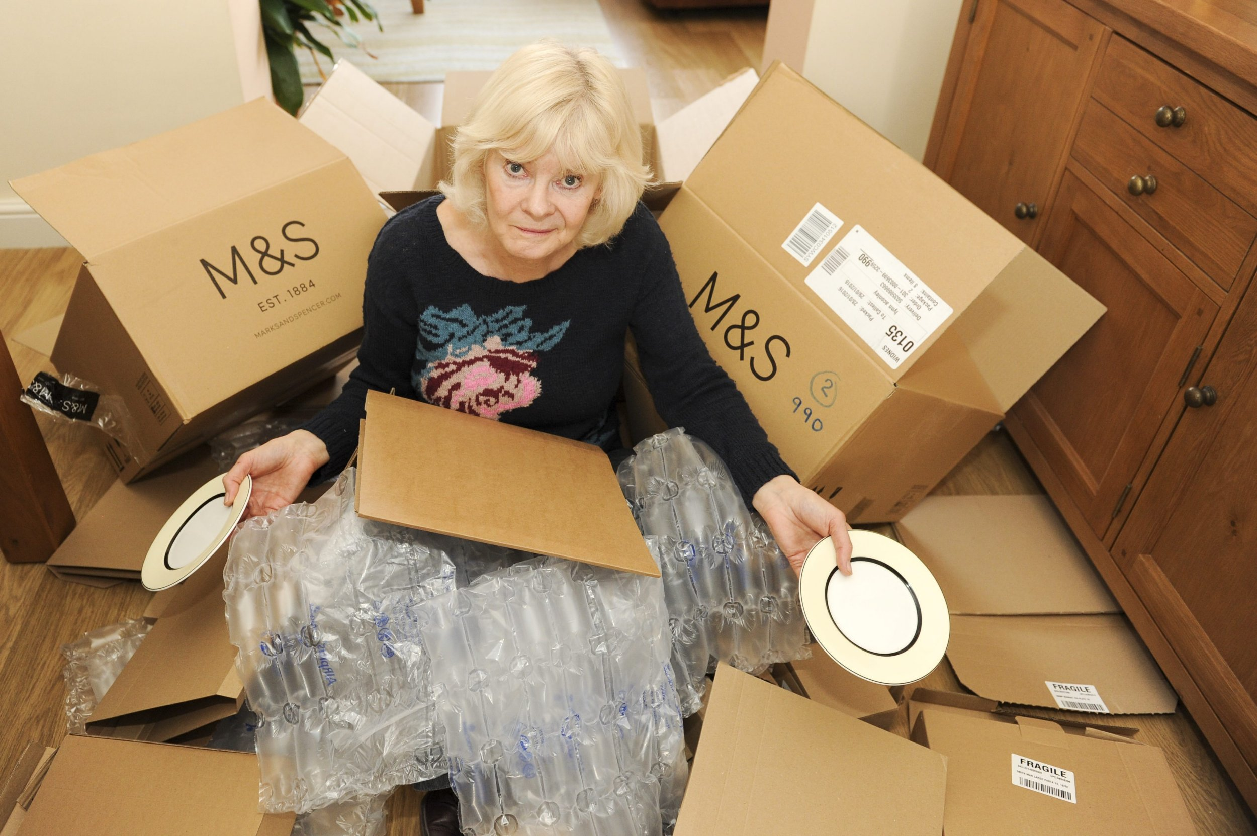 Lynn Aconley, 61, from Liverpool with the packaging. A grandmother who bought a matching dining set from Marks and Spencer was forced to take it home in TWENTY NINE separate boxes after a stock room computer picked up her order as ''separates.''
