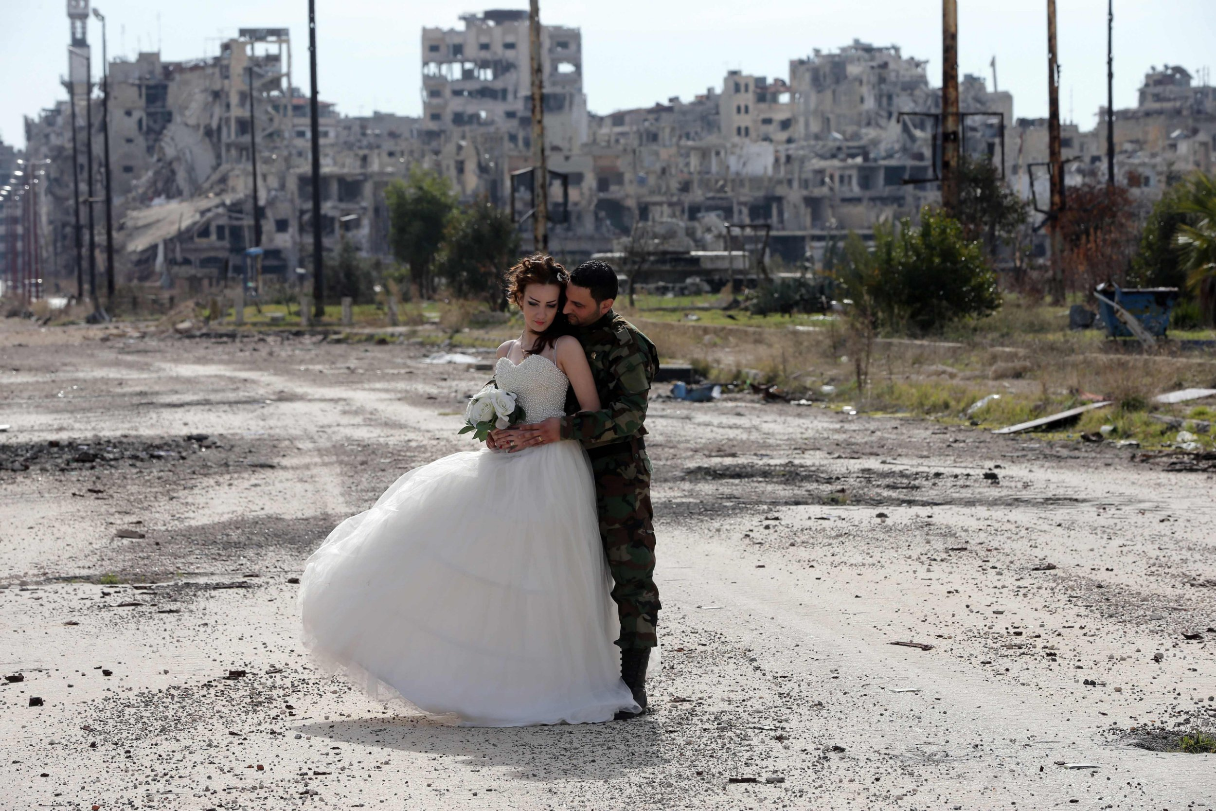 Newly-wed Syrian couple Nada Merhi,18, and Hassan Youssef,27, pose for a wedding picture amid heavily damaged buildings in the war ravaged city of Homs on February 5, 2016. A Syrian photographer thought of using the destruction of Homs to take pictures of newly wed couples to show that life is stronger than death. / AFP / JOSEPH EIDJOSEPH EID/AFP/Getty Images