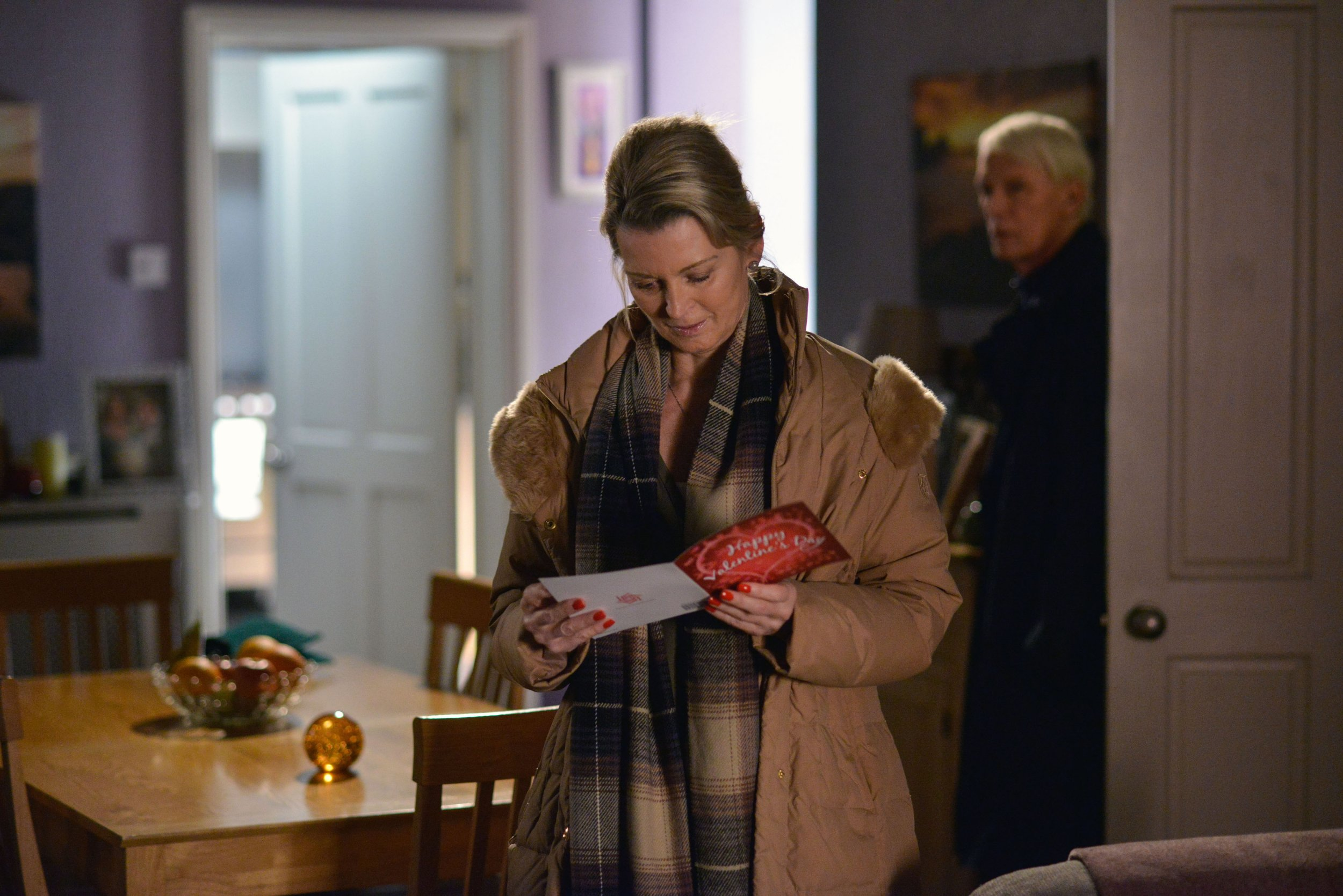 WARNING: Embargoed for publication until 00:00:01 on 09/02/2016 - Programme Name: Eastenders - TX: 15/02/2016 - Episode: 5229 (No. n/a) - Picture Shows: Kathy is puzzled when she finds a card on the table. Kathy Sullivan (GILLIAN TAYLFORTH), Gavin Sullivan (PAUL NICHOLAS) - (C) BBC - Photographer: Jack Barnes