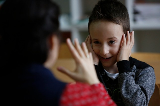 In this photo taken Thursday, Feb. 4, 2016, Bosnian boy Zejd Coralic, right, learns sign language from teacher Anisa Setkic-Sendic in a class at an elementary school in Sarajevo, Bosnia. In 2003, Bosnia adopted laws that allow children with disabilities to be fully integrated into society, including schools. Children with special needs are supposed to have professional assistants who sit with them in class, translating or otherwise helping them participate. But in practice, impoverished Bosnia barely has enough money to keep normal schools functioning and children with disabilities are left to the care and imagination of their parents and the good will of school staff. (AP Photo/Amel Emric)