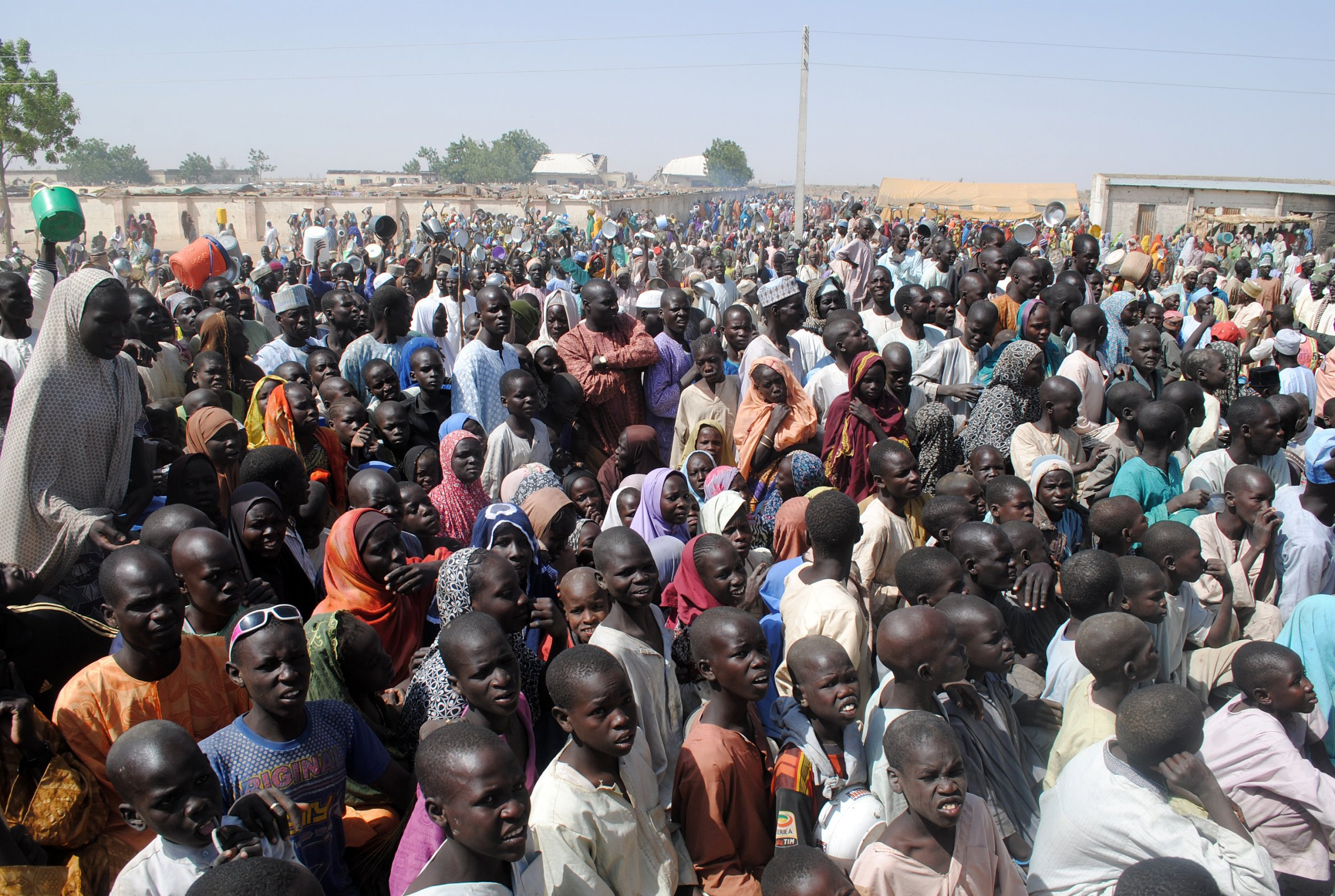 Internally Displaced Persons (IDP) mostly women and children stand waiting for food at Dikwa Camp, in Borno State in north-eastern Nigeria, on February 2, 2016.nThe National Emergency Management Agency in collaboration with Borno State Emergency Management Agency has set up new IDP camps in Ngala, Marte, Bama and Mafa councils to decongest the growing population of IDP camp set up at Dikwa council of Borno State. Nigeria expects many of the 2.1 million people internally displaced by Boko Haram's insurgency to return home in the coming year, amid claims the Islamists are in disarray and a spent force. / AFP / STRINGER        (Photo credit should read STRINGER/AFP/Getty Images)