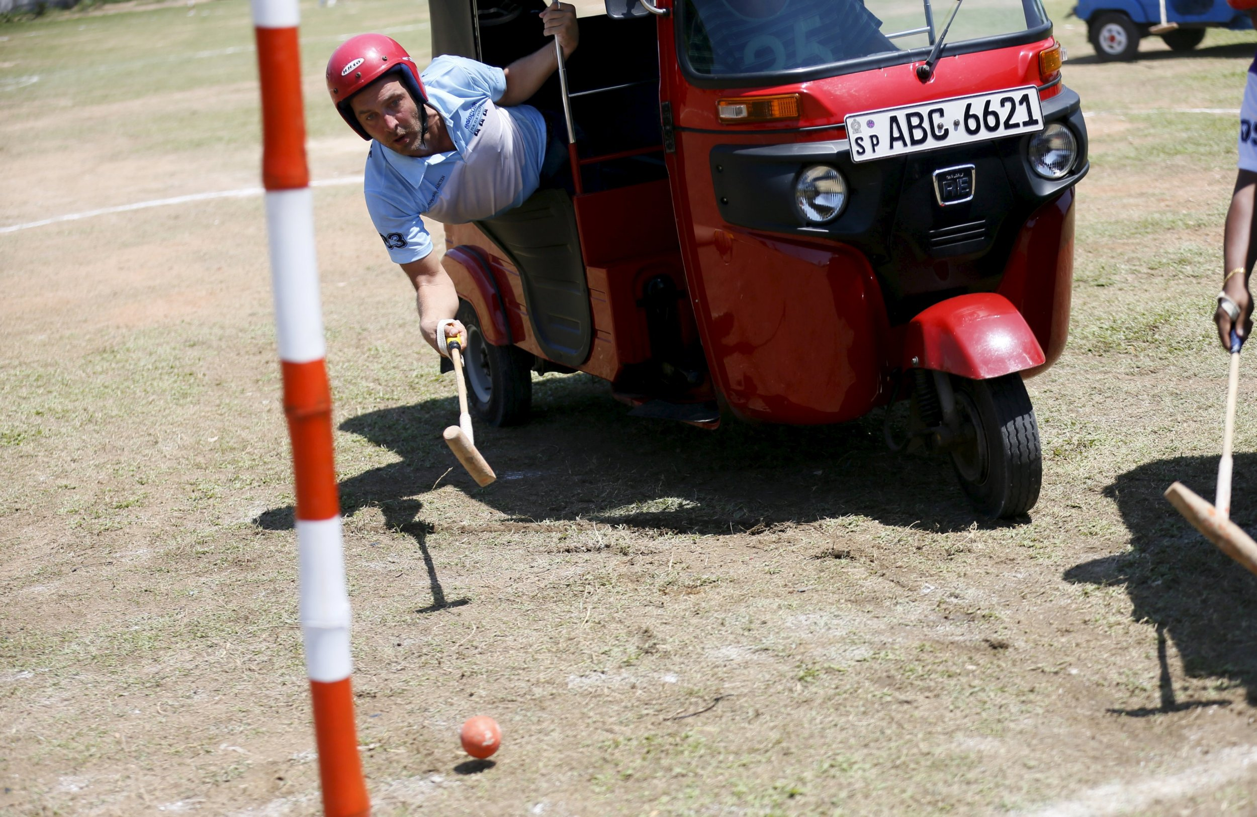 """A competitor hits the ball to get a goal during a """"Tuk Tuk"""" (Three-Wheeled) Polo game in Galle, February 21, 2016. REUTERS/Dinuka Liyanawatte"""