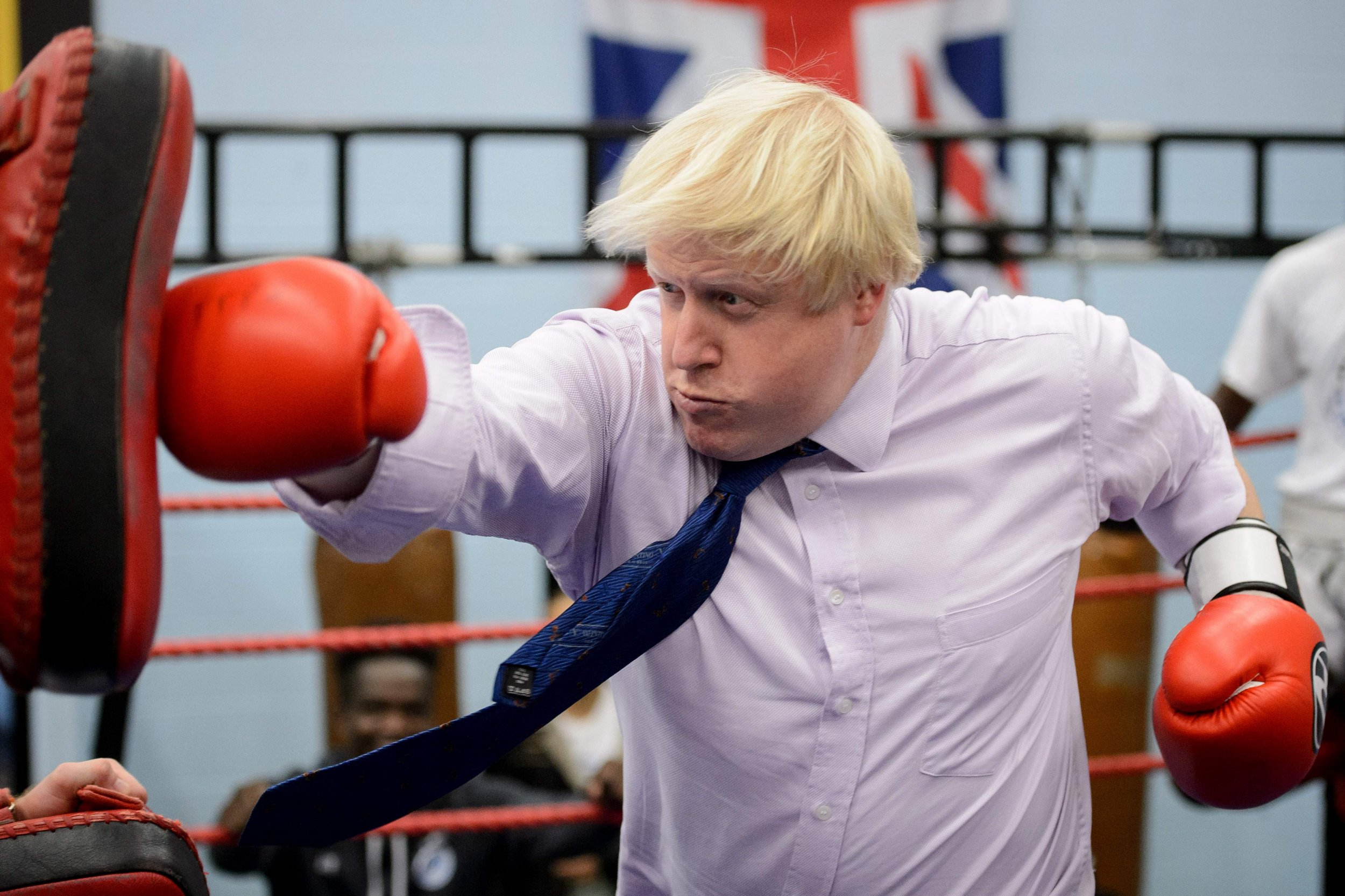 (FILES) This file photo taken on October 28, 2014 shows Mayor of London Boris Johnson boxing with a trainer during his visit to Fight for Peace Academy in North Woolwich, London, on October 28, 2014. London Mayor Boris Johnson has long been both ally and nemesis to Britain's Prime Minister David Cameron but could deal his old friend the heaviest blow yet on February 21, 2016 if he backs the campaign to leave the EU. / AFP / LEON NEALLEON NEAL/AFP/Getty Images