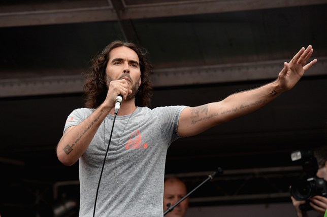 LONDON, ENGLAND - JUNE 20: Comedian Russell Brand speaks to thousands of demonstrators gathered in Parliament Square to protest against austerity and spending cuts on June 20, 2015 in London, England. Thousands of people gathered to march from the City of London to Westminster, where they listened to addresses from singer Charlotte Church and comedian Russell Brand as well as Len McCluskey, general secretary of Unite and Sinn Fein's Martin McGuinness. (Photo by Mary Turner/Getty Images)