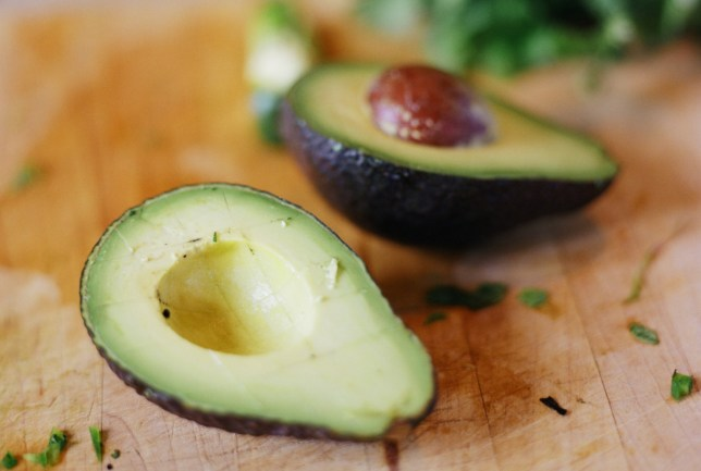 Avocado on cutting board (focus on cross-section in foreground)