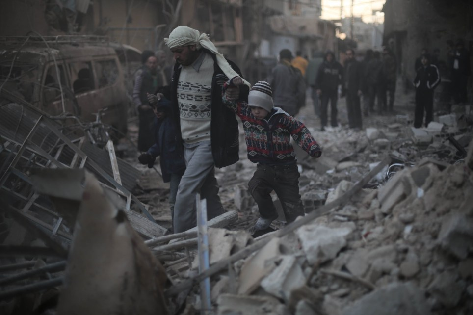 ONE EDITORIAL USE ONLY - NO CROPPING - NO ARCHIVING - MANDATORY CREDIT REQUIRED Undated handout photo issued by Save the Children of a man holding his childs hand as they walk through rubble after surviving an airstrike in Eastern Ghouta, Syria, as the charity launches a new report into life in besieged areas in Syria, where more than 250,000 children remain trapped without food, medicine or electricity. PRESS ASSOCIATION Photo. Issue date: Wednesday March 9, 2016. See PA story POLITICS Syria. Mandatory credit must read: Amer Al Shami/Save the Children/PA Wire NOTE TO EDITORS: Licence restricted for use up to June 9th, 2016 This handout photo may only be used in for editorial reporting purposes for the contemporaneous illustration of events, things or the people in the image or facts mentioned in the caption. Reuse of the picture may require further permission from the copyright holder.