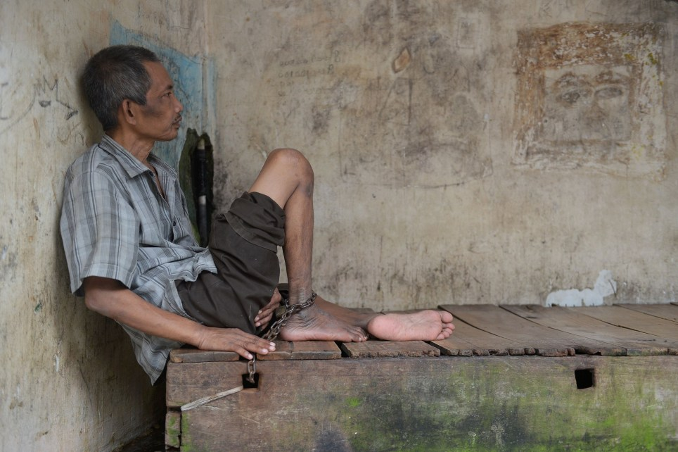 "This picture taken in Brebes on March 16, 2016 shows a mentally ill man resting as they are shackled to their wooden beds at the Bina Lestari Mandiri healing center in Brebes. Human Rights Watch -- who interviewed around 150 people for their report, from the mentally ill to health professionals -- said there are currently almost 19,000 people in Indonesia who are either shackled or locked up in a confined space, a practice known locally as ""pasung"". Chaining up the mentally ill has been illegal in Indonesia for nearly 40 years but remains rife across the country, especially in rural areas where health services are limited and belief in evil spirits prevail, according to HRW. / AFP PHOTO / ADEK BERRY / TO GO WITH AFP STORY INDONESIA HEALTH RIGHTS,FOCUS BY NICK PERRY ADEK BERRY/AFP/Getty Images"