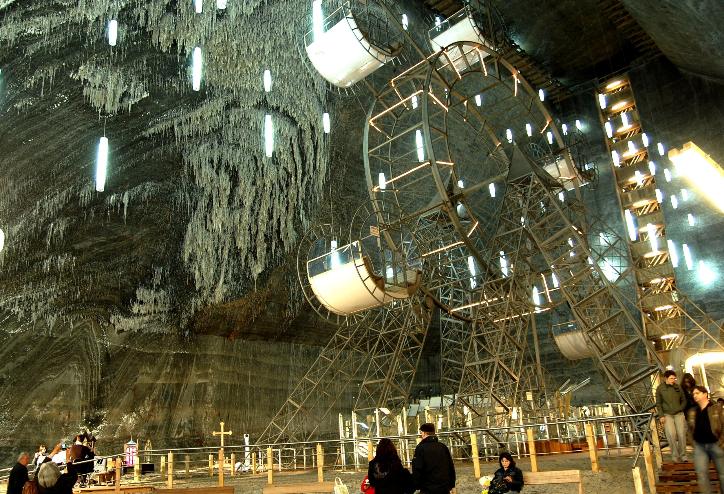 PIC FROM SALINA TURDA / CATERS NEWS - (Pictured: Ferris wheel, at Salina Turda salt mine) - These eye-opening images offer an insight into a gigantic theme park built inside one of the oldest SALT MINES in the world. Salina Turda, in Turda, Romania, regularly features on lists of hidden wonders and, at around 400ft deep, attracts around 600,000 visitors a year. Included in the deep pits list of attractions are a Ferris wheel, boating lake, bowling alley and amphitheatre. Inside the underground world - accessible through a labyrinth of elevators and stairs - the mines walls are also awe-inspiring. - SEE CATERS COPY