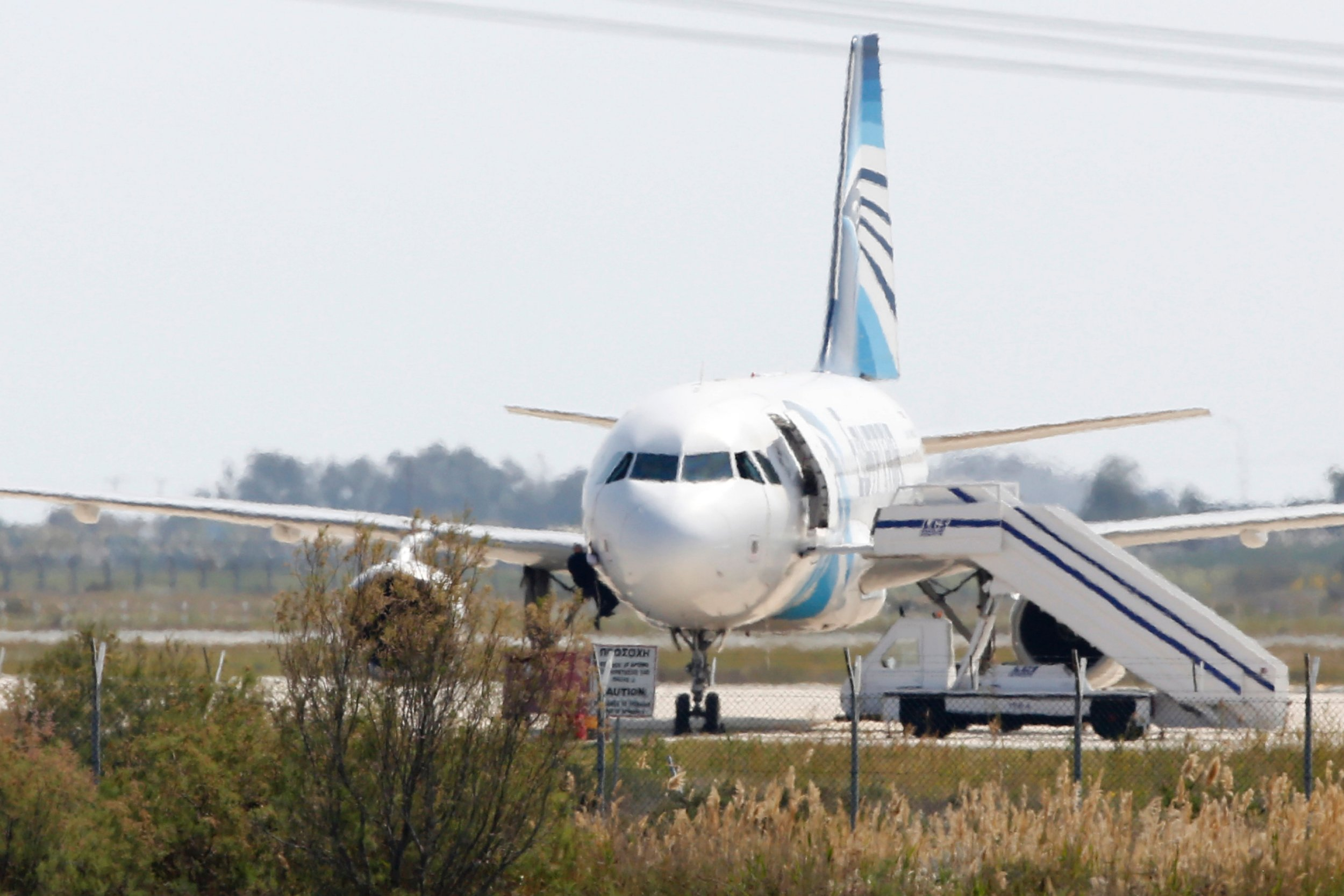 A man climbs out of the cockpit window an EgyptAir Airbus A-320 parked at the tarmac of Larnaca airport after being hijacked and diverted to Cyprus on March 29, 2016. The hijacker who seized the Egyptian airliner and forced it to land in Cyprus has been detained, Cypriot government spokesman Nicos Christodoulides said. / AFP PHOTO / BEHROUZ MEHRIBEHROUZ MEHRI/AFP/Getty Images