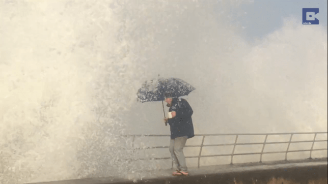 VIDEO wave soaks woman Picture: Caters