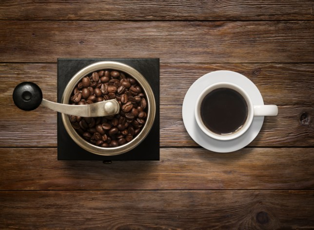 Overhead shot of Coffee Cup and Grinder on Wooden Background