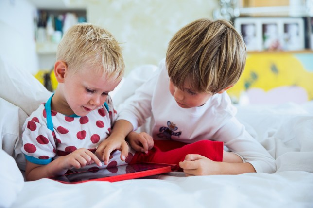 Bothers playing with tablet in bed