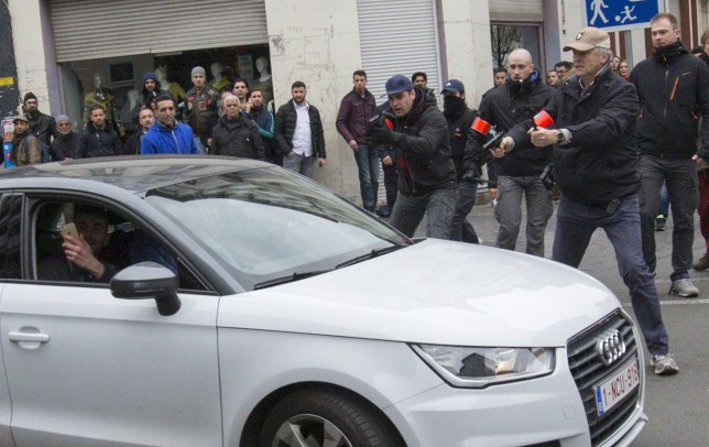 Belgian police point their guns at a car driving towards a police road block before it hit and injured a woman on the street in the Brussels district of Molenbeek, Belgium, April 2, 2016. REUTERS/Yves Herman TPX IMAGES OF THE DAY