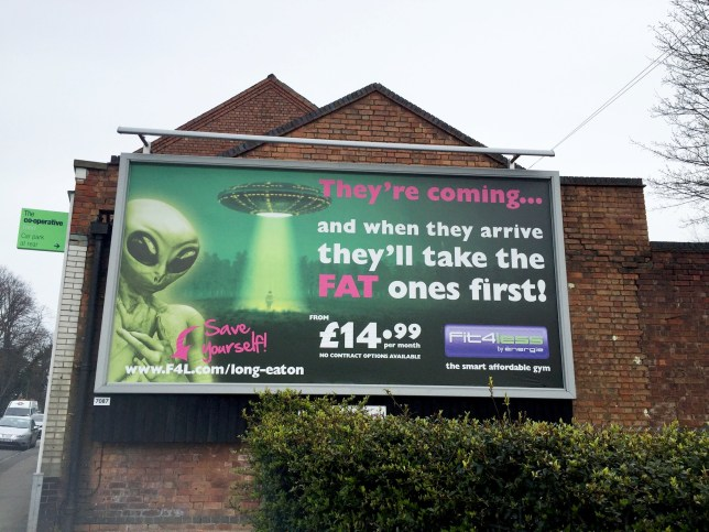 """The Fit4Less gym Long Eatonís billboard on Tamworth Road, Sawley, which has been deemed ëoffensiveí. See NTI story NTIFAT. A national gym chain has been blasted for putting up a giant billboard saying fat people will be abducted by ALIENS. The controversial 20ft-high poster was put up to advertise Fit4Less on the side of a Co-operative store overlooking a busy road. It shows a green alien and a person being beamed up by a green light into a spaceship. The text on the gigantic billboard reads: """"They're coming...and when they arrive they'll take the FAT ones first!"""" It also says """"Save yourself!"""" next to an arrow pointing to the gym's website. Fit4Less has now been criticised for encouraging bullying by putting up the giant advert on Tamworth Road in Sawley, Derbys."""