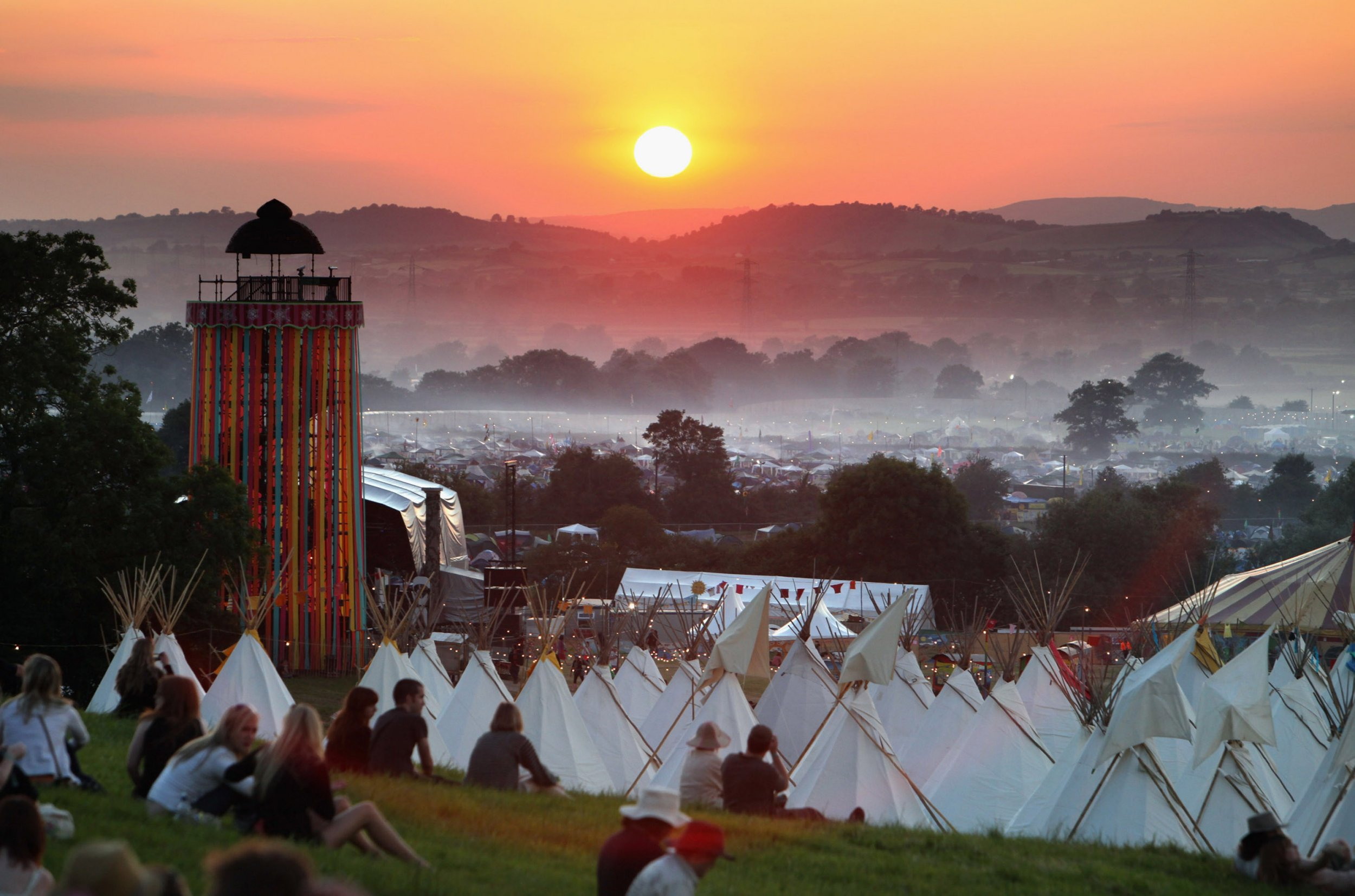 GLASTONBURY, UNITED KINGDOM - JUNE 24: People gather to watch the sunset on a hill above the tipi field as music fans start to arrive at the Glastonbury Festival site at Worthy Farm, Pilton on June 24, 2009 in Glastonbury, Somerset, England. The gates have opened for the first of the 140000 music fans arriving, at what has become one of Europe's largest music festivals, but weather forecasters have warned that bad weather may be on the way. (Photo by Matt Cardy/Getty Images)