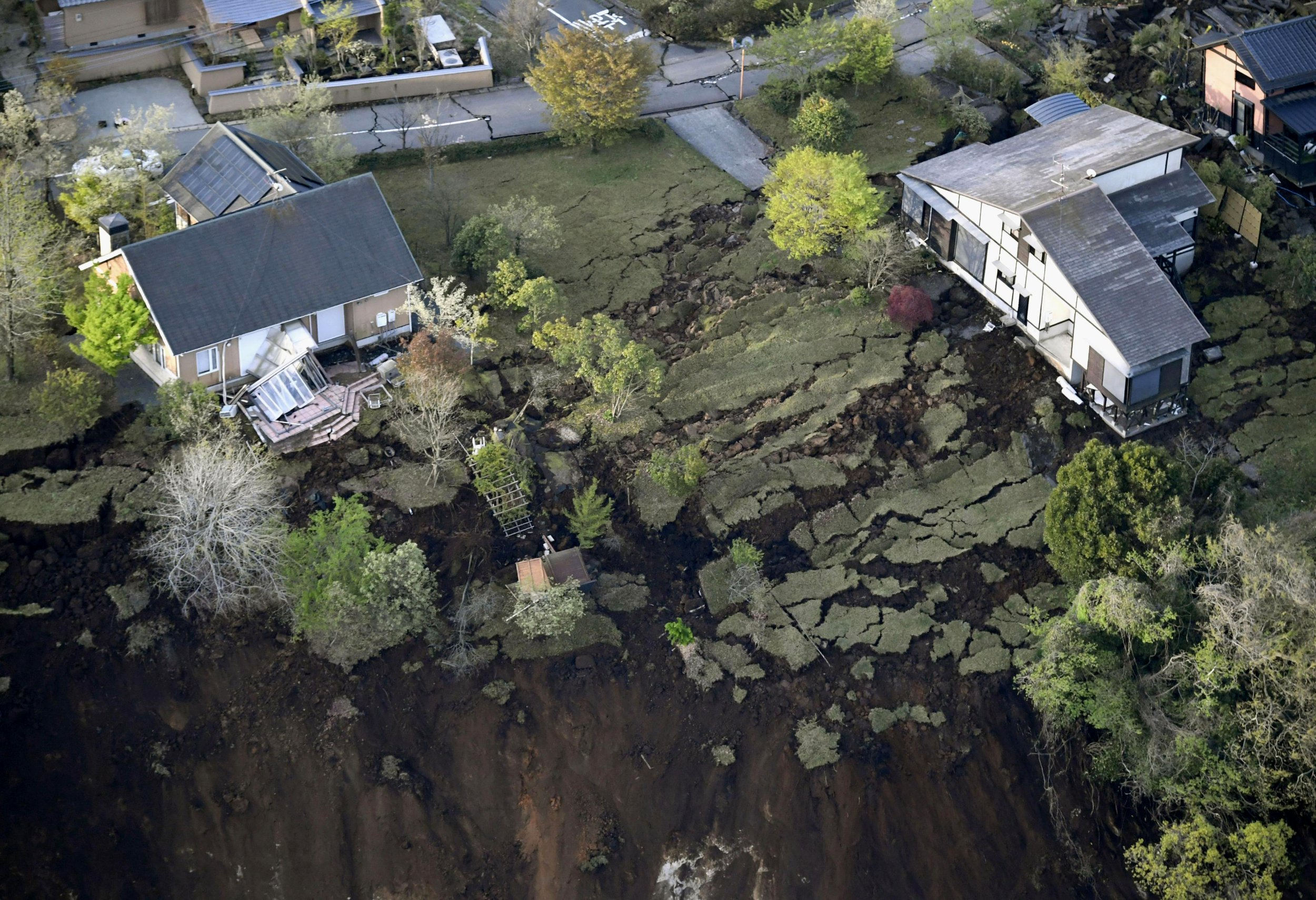 Houses are seen in a landslide-hit area in Minamiaso, Kumamoto prefecture, southern Japan Saturday, April 16, 2016. A powerful earthquake struck southern Japan early Saturday, barely 24 hours after a smaller quake hit the same region. (Kyodo News via AP) JAPAN OUT, MANDATORY CREDIT