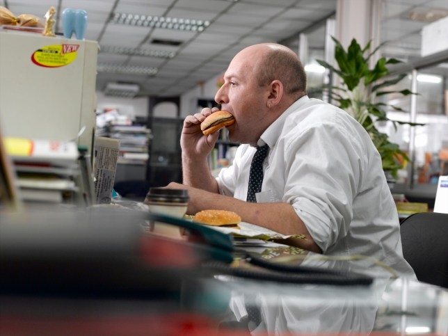 Male office worker eating burgers at desk, profile