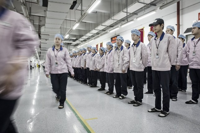 Employees make their way to the assembly line area after lining up for roll call at a Pegatron Corp. factory in Shanghai, China, on Friday, April 15, 2016. This is the realm in which the world's most profitable smartphones are made, part of Apple Inc.'s closely guarded supply chain. Photographer: Qilai Shen/Bloomberg via Getty Images