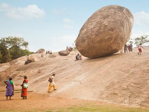 Tourists tempt fate posing under gravity-defying boulder