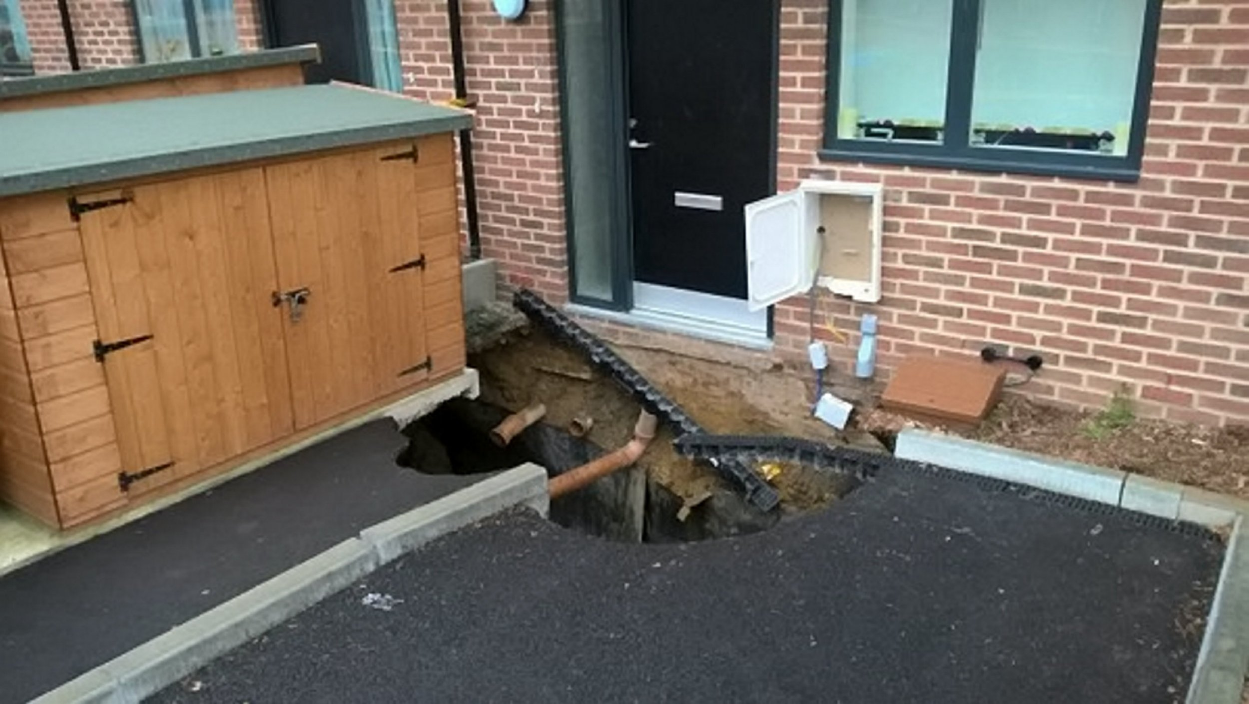 The sinkhole in Plumstead, south east London. See SWNS story SWSINK; Residents of a brand new housing development were evacuated this weekend - after a SINKHOLE emerged. The deep hole emerged outside a block of properties that were recently erected and lead to 48 people being forced out of their homes on bank holiday Monday. London Fire Brigade cordoned off the area around Brickfield Cottages, in Plumstead, south east London as a 'hazard zone'. The cause of the enormous hole, which measures 5 metres by 5 metres, is currently unknown.