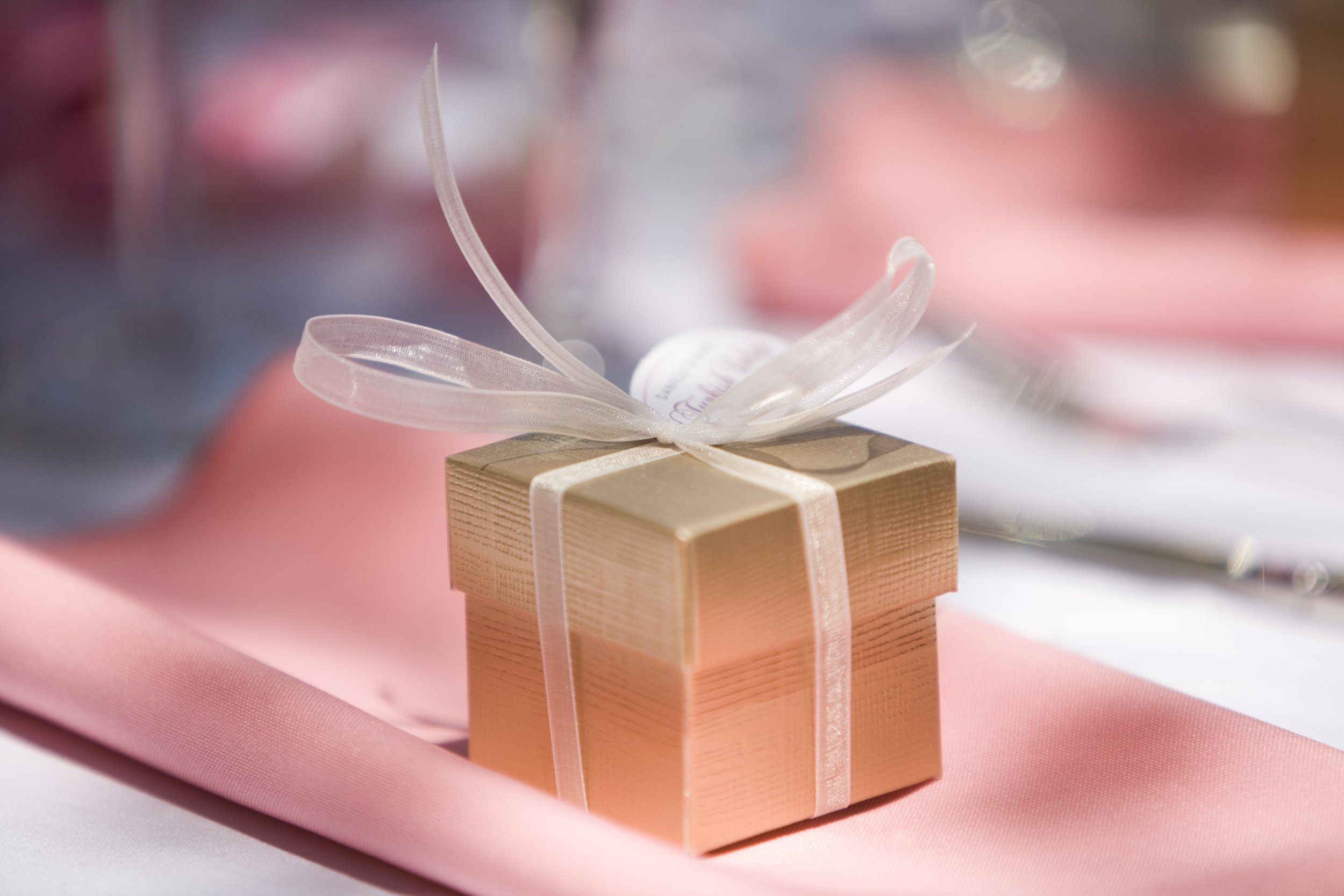gold party favor gift box at wedding reception on top of pink napkin