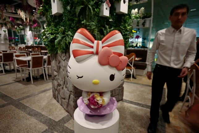 epa05300824 A staff member walks past a statue of Hello Kitty during the opening of the Hello Kitty Cafe at Changi Airport in Singapore, 12 May 2016. The cafe sells an assortment of Hello Kitty themed products as well as food items and will stay open 24 hours around the clock, the first of it's kind worldwide. EPA/WALLACE WOON