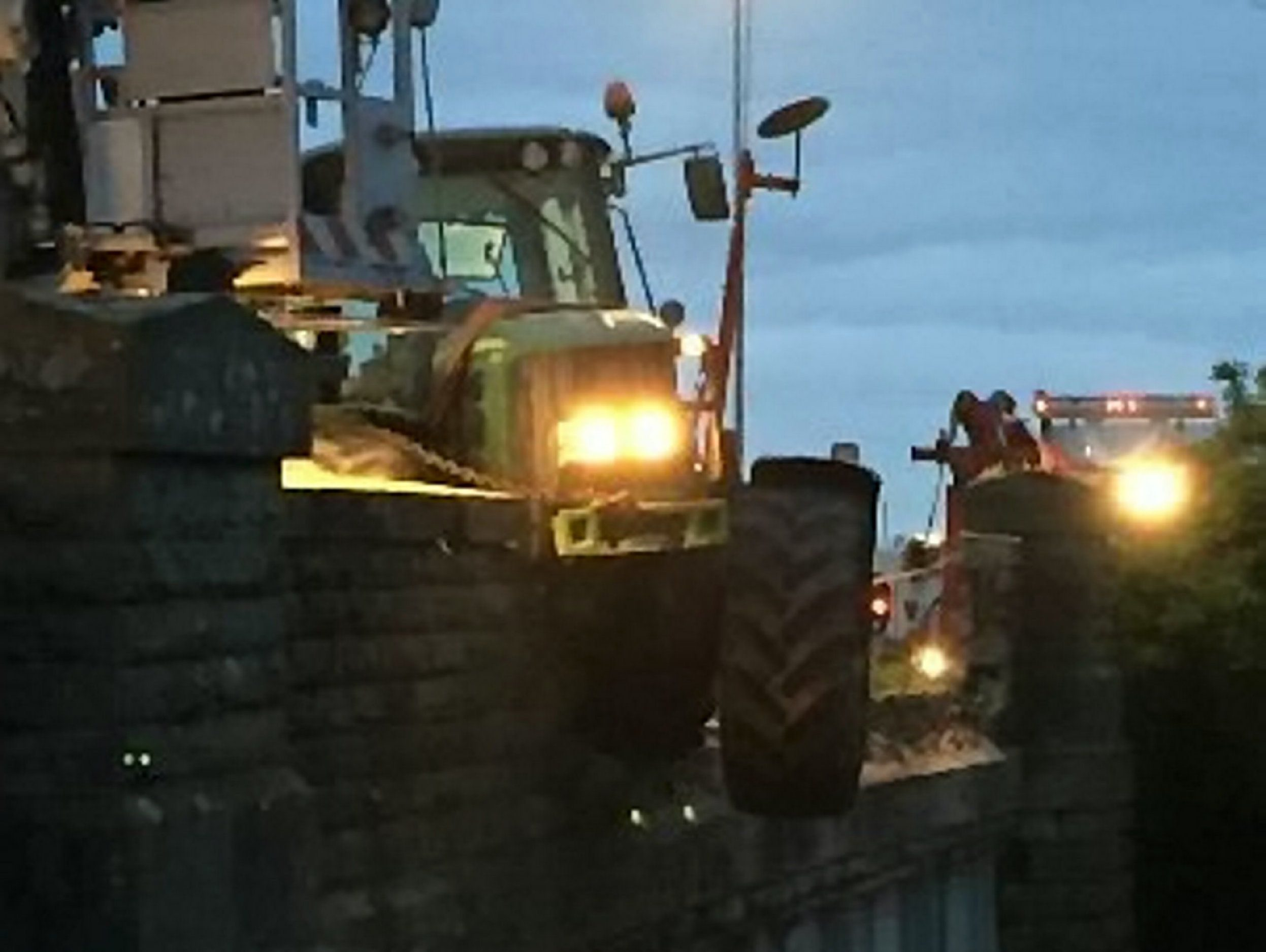 A stolen John Deere tractor crashed on a Victorian bridge over a railway at Abbotswood, near Worcester. See Newsteam story NTITRACTOR; Police are hunting a thief who caused a train to crash after he smashed a stolen tractor into a railway bridge - while hitting a top speed of 7mph. Dramatic pictures show the nine-tonne John Deere tractor hanging precariously over the edge of the bridge. Despite having a top speed of just 7mph, the impact of the crash sent tonnes of rubble onto the track just moments before a train passed packed with passengers. Incredibly, despite the Cardiff to Birmingham New Street train hitting the rubble, it was not de-railed and no one was injured. The drama unfolded at 9.30pm on Friday (13/5) when the tractor careered into a Victorian road bridge at Abbotswood, near Worcester.
