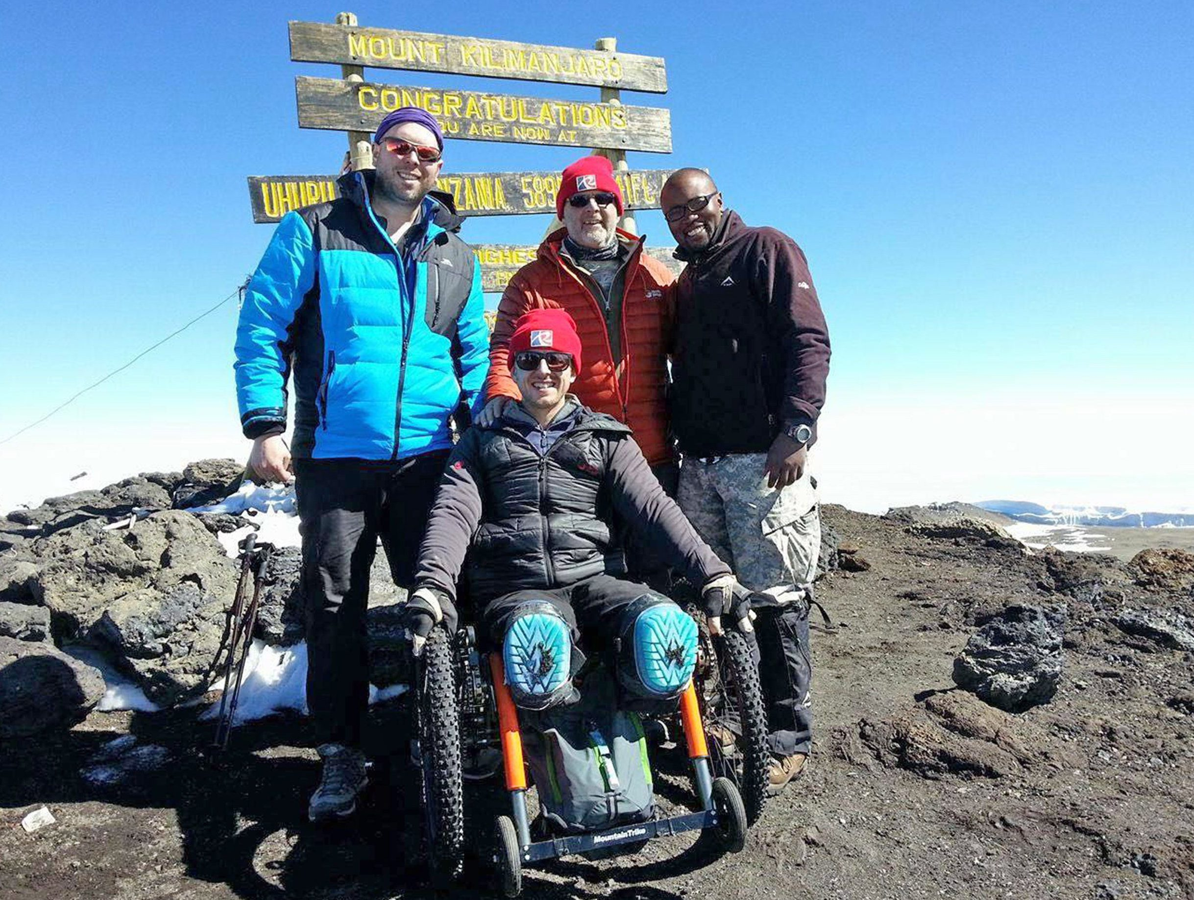 A double amputee was today celebrating after scaling Mount Kilimanjaro in a wheelchair. Aaron Phipps, 33, who tragically lost both legs and the tips of his fingers when he developed meningitis as a teenager, became the first Brit to manage the remarkable feat. Despite his disability he was undeterred in his quest to climb the 19,341ft tall mountain above Tanzania in Africa - the highest on the continent. Aaron, a team GB paralympic star who was a member of the wheelchair basketball team at London 2012, has never let his disability affect him. SEE OUR COPY FOR DETAILS. Pictured: Aaron reaches the summit Please byline: Team Kilimanjaro/Solent News © Team Kilimanjaro/Solent News & Photo Agency UK +44 (0) 2380 458800