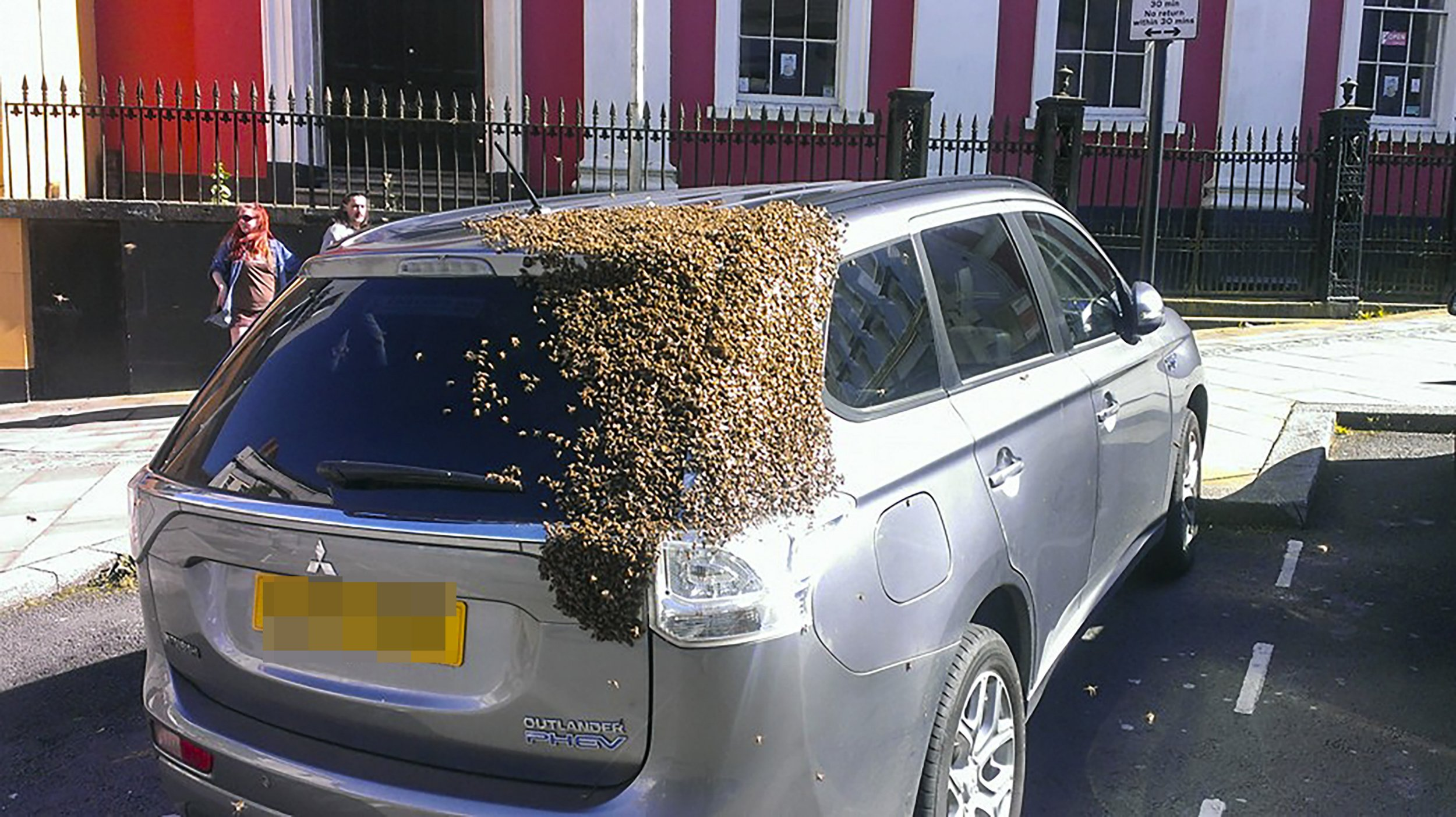 PIC BY TOM MOSES/MERCURY PRESS (PICTURED: THE BEES TAKEN UP RESIDENCE ON A 4X4 CAR PARKED IN A CAR PARK IN HAVERFORDWEST, SOUTH WEST WALES) A ëlostí swarm of bees sparked chaos in a high street when their queen got stuck in a car boot ñ resulting in 20,000 bees chasing the 4x4 for TWO DAYS. Dad-of-one Tom Moses, 41, spotted the unusual sight while driving through Haverfordwest, south west Wales, around 5pm on Sunday evening and decided to stop to help out. However it took a procession of FIVE different beekeepers, park rangers and passers-by to coax them off into a cardboard box, only for the wind to blow it off the car and the queen go back to the boot. Roger Burns of Pembrokeshire Beekeepers then says the carís owner returned and drove away with the queen unknowingly trapped in the back, resulting in the swarm taking up the chase the next day. SEE MERCURY COPY