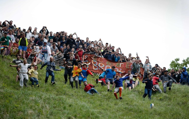 Competitors tumble down Cooper's Hill in pursuit of a round Double Gloucester cheese (Below R) during the annual Cooper's Hill cheese rolling competition near the village of Brockworth, Gloucester, in western England, on May 30, 2016. The annual Cooper's Hill Cheese Rolling involves competitors chasing an eight pound Double Gloucester cheese down a steep hill. The slope has a gradient in places of 1-in-2 and in others 1-in-1, its surface is very rough and uneven and it is almost impossible to remain on foot for the descent. The winner of the downhill race wins the cheese. / AFP PHOTO / ADRIAN DENNISADRIAN DENNIS/AFP/Getty Images