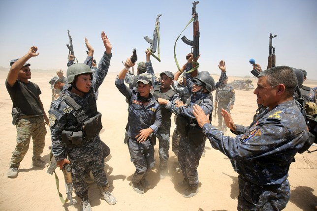Pro-government forces fighters celebrate in the al-Sejar village, in Iraq's Anbar province, on May 27, 2016, as they take part in a major assault to retake the city of Fallujah, from the Islamic State (IS) group. Hundreds of people fled the Fallujah area with the help of Iraqi forces who are fighting to retake the city from the Islamic State jihadist group, officials said. Iraqi forces launched an operation to recapture Fallujah, an IS stronghold located just 50 kilometres (30 miles) west of Baghdad, at the start of this week. / AFP / AHMAD AL-RUBAYE (Photo credit should read AHMAD AL-RUBAYE/AFP/Getty Images)