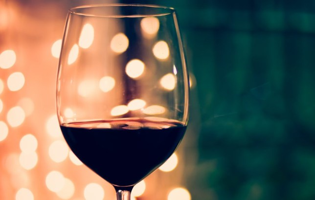 Close up of glass of red wine at night, with shallow depth of field and out of focus lights in background.