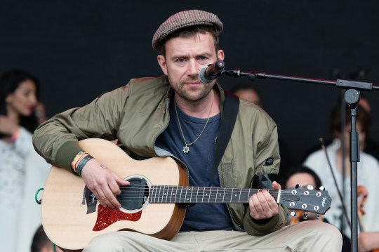 Damon Albarn sitting down as he plays the guitar at Glastonbury in 2016