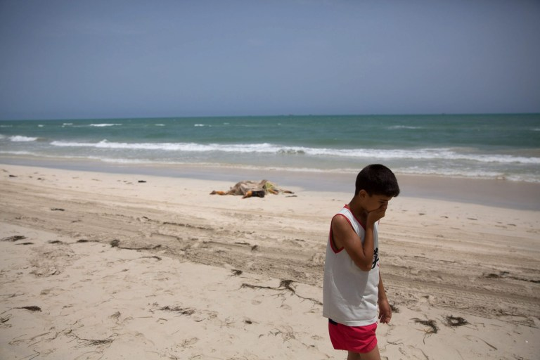 epa05343244 A boy walks on a beach where bodies of migrants washed up, in Zuwarah, west of Tripoli, Libya, 02 June 2016. According to media reports citing Red Crescent officials, at least 85 bodies have washed up onto Libyan beaches this week. EPA/MOHAME BEN KHALIFA ATTENTION EDITORS: GRAPHIC CONTENT
