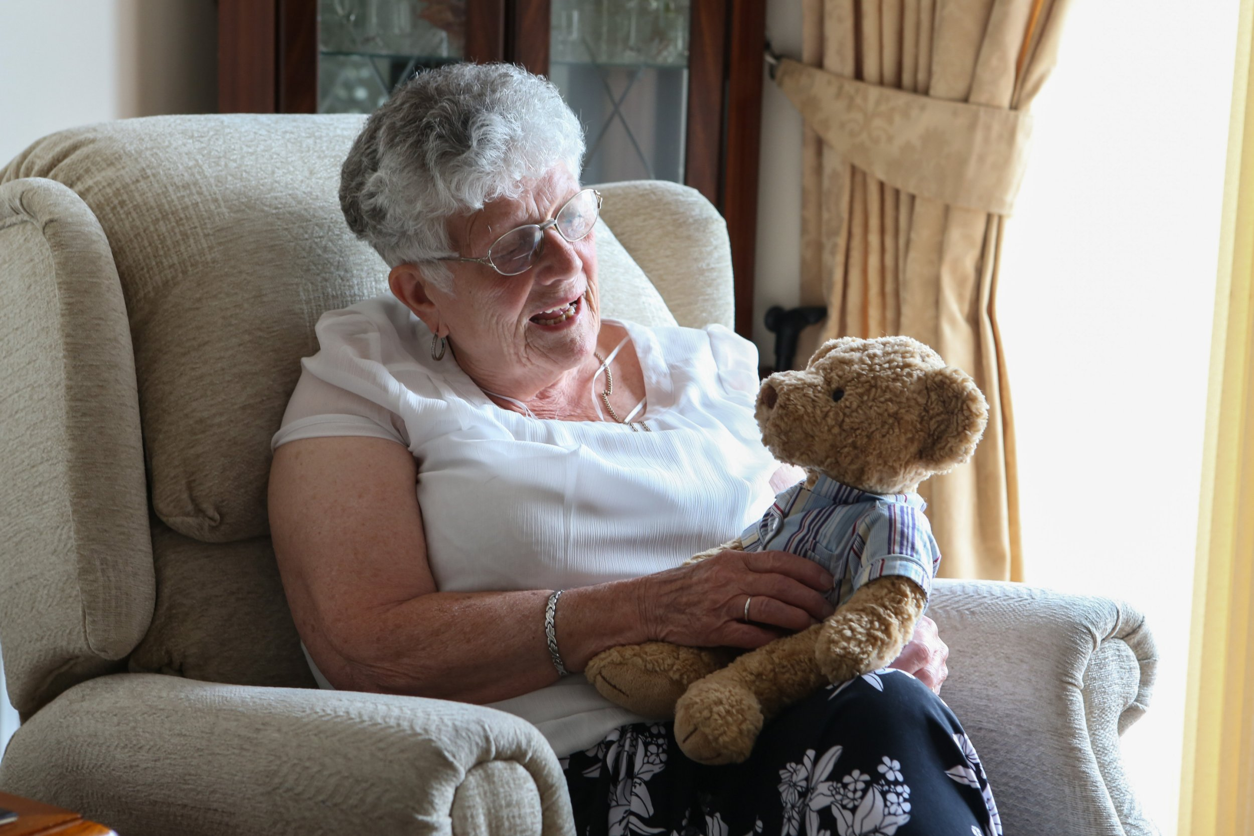 "Jean Walters with the teddy bear which has a chip with her late husband's voice in it. See SWNS story SWTEDDY; Jean Walters was originally given the cuddly bear by her granddaughter Abbie Webb ten years ago, a month before her husband Dennis died of lung cancer in 2005. When squeezed, the soft toy plays a clip of Dennis saying: ""You're the best girl in the world for me,"" - something he wrote in letters to Jean during his time in the Army. Grandmother-of- Jean, a retired xxxx who was diagnosed with dementia in xxxx, would listen to the soundbite every day to feel close to her sweetheart."