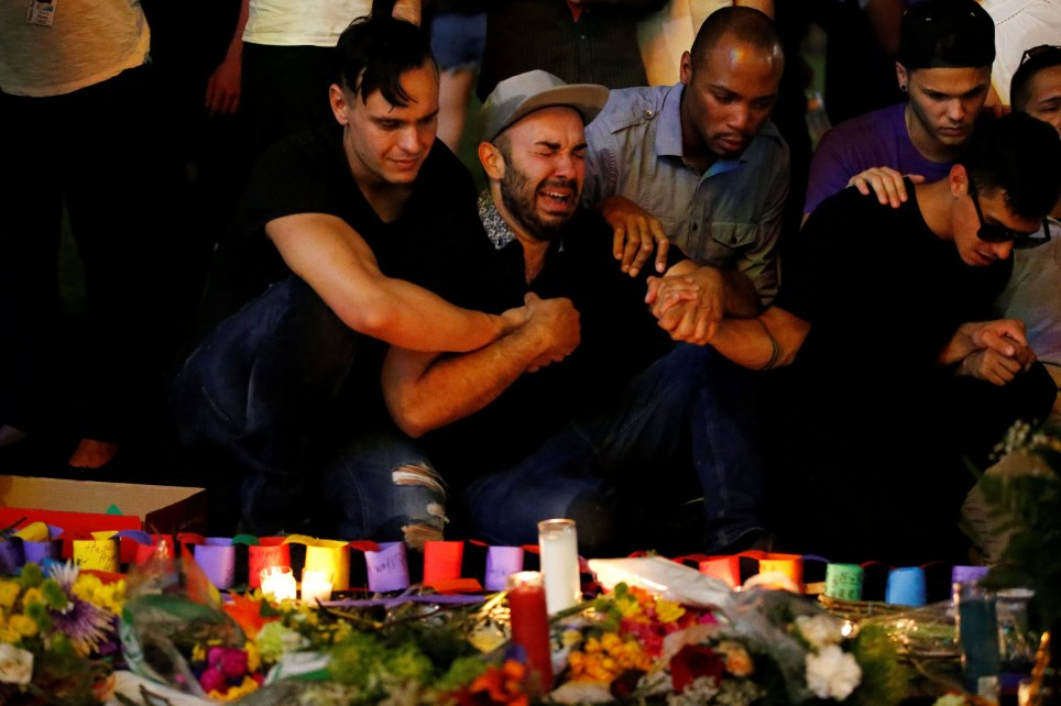 A man sits and cries after taking part in a candlelight memorial service the day after a mass shooting at the Pulse gay nightclub in Orlando, Florida, U.S. June 13, 2016. REUTERS/Carlo Allegri