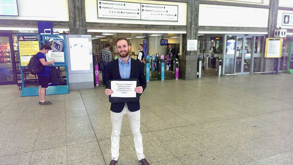 """This man is standing in Cardiff Central train station with a sign asking commuters for a job. We went to speak to Thomas Tilley, 25, while he was in the station on Monday morning with the sign reading: """"Business Graduate. Seeking career opportunities. Please ask for CV. Diolch."""""""