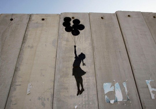 A Banksy artwork on a security barrier in the West Bank, featuring a young girl being lifted to the skies by balloons - painted all in black