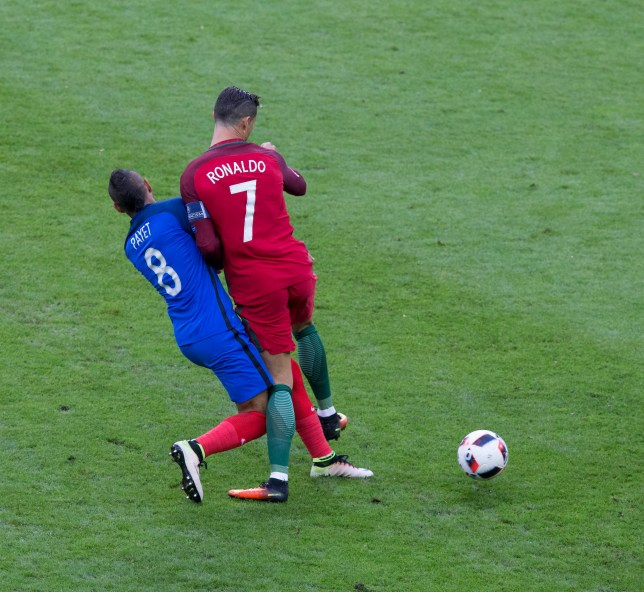 PARIS, FRANCE - JULY 10:  France's Dimitri Payet with a heavy challenge on Portugal's Cristiano Ronaldo during the UEFA Euro 2016 Final match between Portugal and France at Stade de Lyon on July 10 in Paris, France.  (Photo by Craig Mercer/CameraSport via Getty Images)