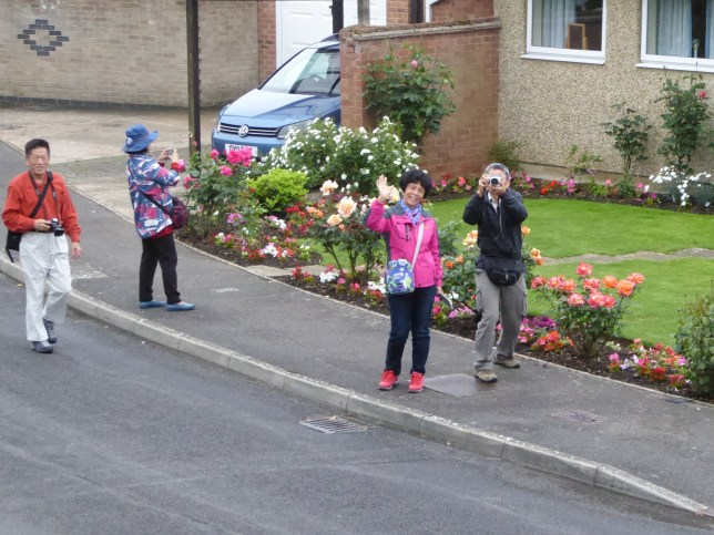 Collect photo of some of the Chinese and Japanese tourists who have been spotted in a very ordinary residential street in Kidlington, Oxon. See SWNS story SWTOURIST; Clueless residents of an English village have been left baffled following an influx of 'sight-seeing' foreign tourists arriving by the coachload - for no apparent reason. Stunned locals say hoards of Chinese and Japanese holidaymakers began arriving in Kidlington, Oxon., on tour buses three weeks ago. The camera-totting tourists have been wandering around the rural village in groups of up to 40 at a time - taking photos of houses and gardens. Tourists have even knocked on doors along 'unremarkable' Benmead Road and The Moors road and asked for pictures of locals - before taking selfies with them.