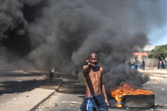 (FILES) This file photo taken on July 06, 2016 shows a protester shouting anti-Mugabe slogans in front of burning tyres during a demonstration on July 6 2016, in Makokoba, Bulawayo Zimbabwe. Street protests, national work boycotts and internet activism are on the rise in Zimbabwe -- offering hints that opposition to ageing President Robert Mugabe could be building towards a boiling point. / AFP PHOTO / --/AFP/Getty Images