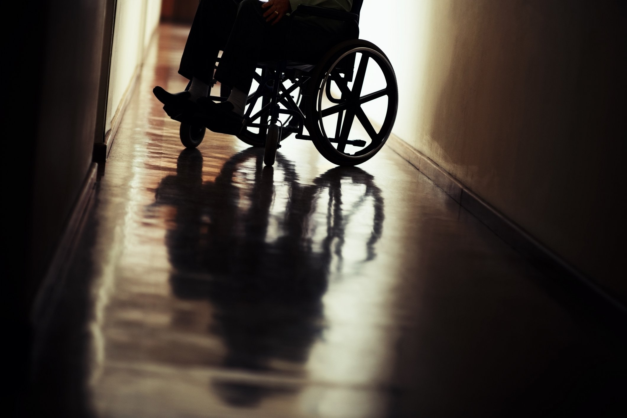 Low section silhouette of handicapped man sitting on wheelchair in hospital hallway